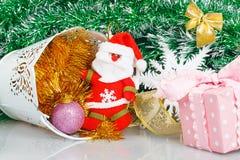 有白色桶、桃红色礼物盒和白色雪花的圣诞老人 免版税库存图片