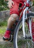 有白色棉花选矿绷带的男孩在自行车 免版税库存图片