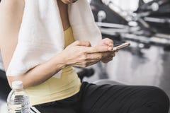 有白色毛巾的亚裔女运动员使用智能手机 免版税库存照片