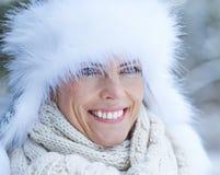 有白色毛皮盖帽的妇女在冬天 免版税库存照片