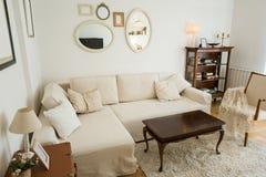 有白色沙发和葡萄酒装饰的明亮的客厅 免版税图库摄影