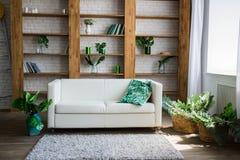 有白色沙发的一个木机架在它旁边 图库摄影