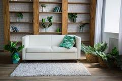 有白色沙发的一个木机架在它旁边 库存照片