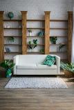 有白色沙发的一个木机架在它旁边 库存图片