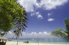 有白色沙滩、水晶蓝色海水和多云蓝天的美丽的热带海岛晴天 库存照片