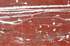 有白色油漆滴水、下落和污点的褐红的混凝土墙 免版税图库摄影