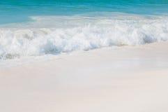 有白色波浪和白色沙子的绿松石海 库存照片