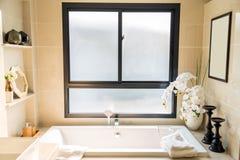 有白色浴缸和白色毛巾机智的豪华biege卫生间 库存照片