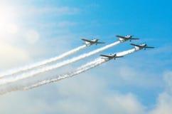 有白色烟飞行踪影的轻的引擎飞机在小组的在与阳光和强光的蓝天 免版税库存图片