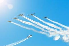 有白色烟飞行踪影的轻的引擎飞机在小组的在与阳光和强光的蓝天 库存照片