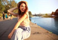 有白色牙的妇女认为和看斜向一边在一个公园的在夏天 免版税库存照片