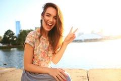 有白色牙的妇女认为和看斜向一边在一个公园的在夏天 免版税图库摄影