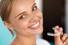 有白色牙的微笑的妇女握牙漂白盘子的 图库摄影