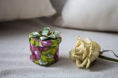 有白色玫瑰的礼物盒在长沙发 免版税库存图片
