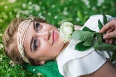 有白色玫瑰的美丽的女孩 免版税库存图片