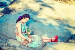 有白色玫瑰的年轻美国妇女,坐岩石,放松 库存图片