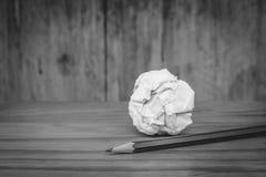 有白色的使用的铅笔弄皱了在木地板上把放的纸球在黑白图象 免版税库存照片