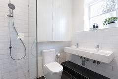 有白色盖瓦的小ensuite卫生间在砖样式放置了 库存照片
