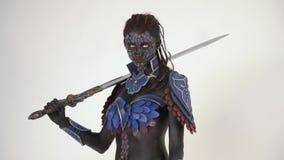 有白色眼睛的一个黑暗的战士拿着在她的肩膀的剑并且转向照相机 影视素材