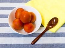 有白色碗的木匙子用在黄色安置的五个蕃茄 库存照片