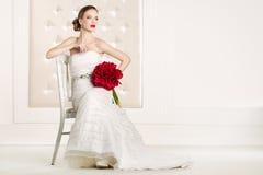 有白色礼服的华美的新娘有红色的开花花束 免版税库存照片