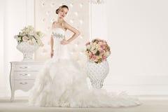 有白色礼服的华美的新娘有花花束的 免版税库存照片