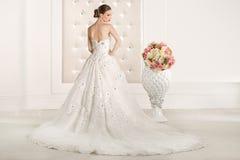 有白色礼服的华美的新娘有花花束的 免版税库存图片