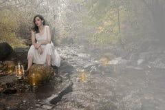 小河的妇女与蜡烛 免版税库存照片