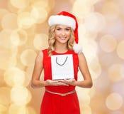 有白色空白的购物袋的微笑的妇女 免版税库存照片