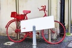 有白色空的海报的红色自行车 库存照片