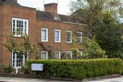 有白色窗口的两层砖房子 安静的区域在伦敦中部,有树篱的前面庭院,春天,开花 免版税图库摄影