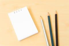 有白色笔记本的三支铅笔在浅褐色的木表上 免版税库存照片