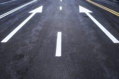 有白色箭头标志的柏油路 免版税库存图片