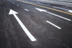 有白色箭头标志的柏油路 库存照片