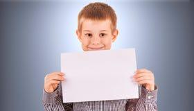 有白色纸片的滑稽的逗人喜爱的男孩 免版税图库摄影