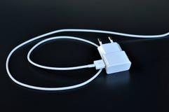 有白色缆绳和插座的AWhite手机充电器在黑背景 免版税库存照片
