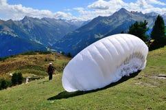 有白色翼的滑翔伞准备好跳跃从山 免版税库存图片