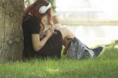 有白色耳机和智能手机的Defocused红色顶头年轻女人在手上在树下坐绿草 库存照片