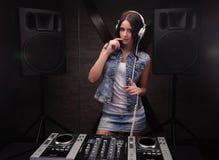 有白色耳机的Dj妇女在她的头 在背景的扩音器 库存图片