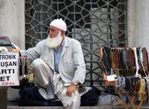 有白色胡须的土耳其年长人在入口附近卖在街道上的回教念珠tasbih到清真寺 库存照片