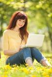有白色膝上型计算机的逗人喜爱的妇女在公园 免版税库存照片
