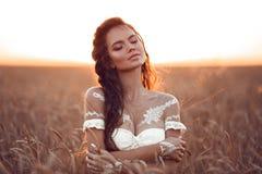 ( 有白色艺术的摆在麦田享用在日落的漂泊女孩画象  户外照片 ?? 免版税库存图片