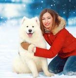 有白色萨莫耶特人狗的圣诞节画象愉快的微笑的妇女在雪在冬日 免版税库存照片
