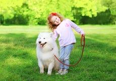 有白色萨莫耶特人狗的愉快的孩子在草 免版税库存图片