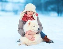 有白色萨莫耶特人狗的愉快的少年男孩户外在冬日 免版税库存图片