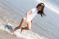有白色衬衣的女孩走在海滩 库存图片