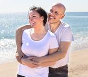 有白色衬衣的拥抱在bea的沙子的一名妇女的年长人 免版税库存图片