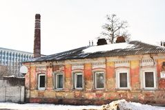 有白色装饰品的老红砖管子,有破旧的桃红色房子的住宅区和在背景的行政大厦 库存图片