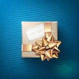 有白色贺卡的米黄礼物盒和与在蓝色背景隔绝的丝带的闪烁的金黄弓 免版税库存图片