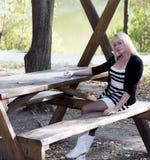 有白色起动的金发碧眼的女人在湖的一张木桌上 库存图片
